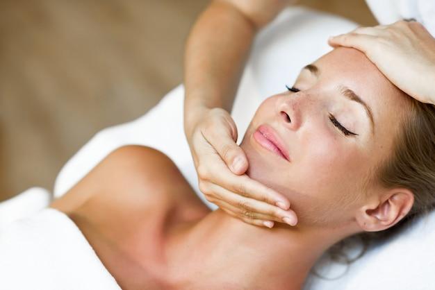 Jonge vrouw krijgt een hoofdmassage in een spa-centrum. Gratis Foto