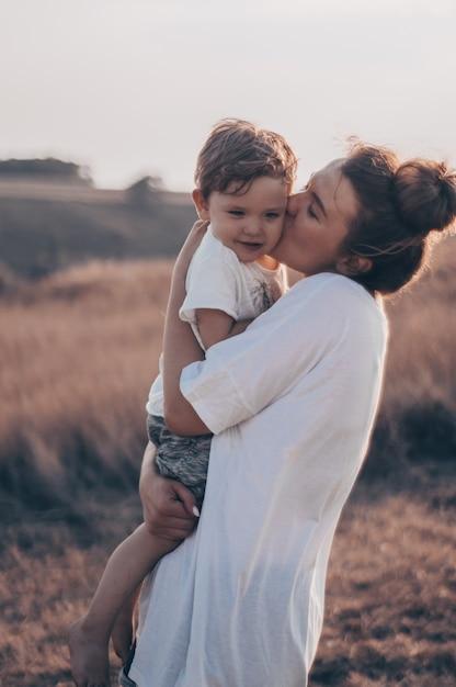 Jonge vrouw kust haar zoontje op zonnig in de wei bij zonsondergang. jonge moeder die haar baby houdt. moeder en zoontje hebben een goede tijd in de natuur. kleur getinte afbeelding Premium Foto
