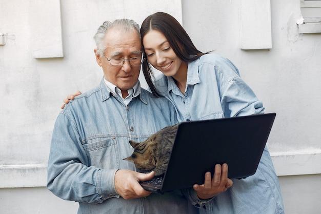 Jonge vrouw leert haar grootvader hoe een laptop te gebruiken Gratis Foto