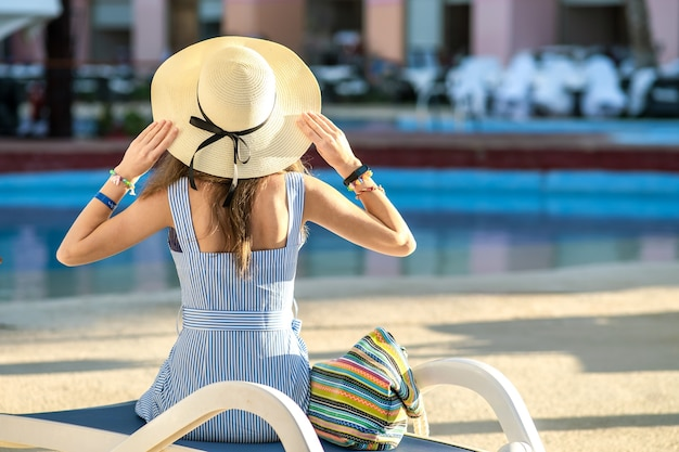 Jonge vrouw lichte zomerjurk en gele stro hoed dragen buiten zitten in de buurt van het zwembad van het hotel op zonnige zomerdag. Premium Foto