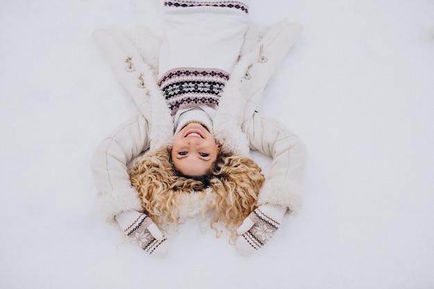 Jonge vrouw liggend op sneeuw in park Gratis Foto