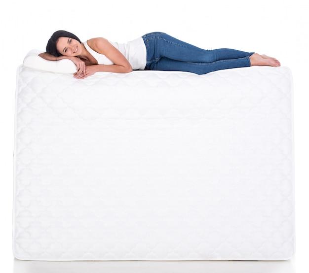 Jonge vrouw ligt op de matras. Premium Foto
