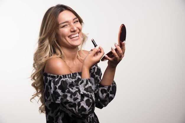 Jonge vrouw lippenstift met gelukkige uitdrukking toe te passen. Gratis Foto