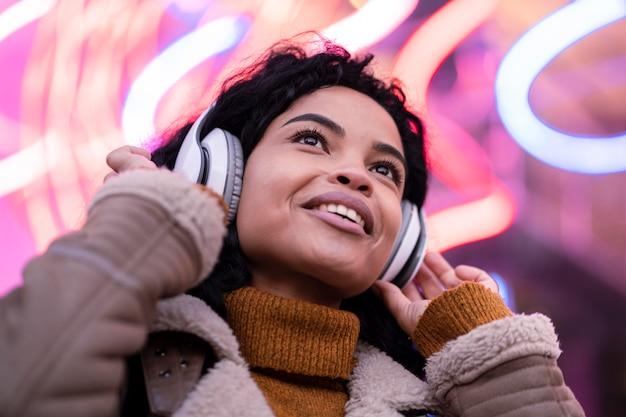 Jonge vrouw luisteren naar muziek via een koptelefoon Gratis Foto