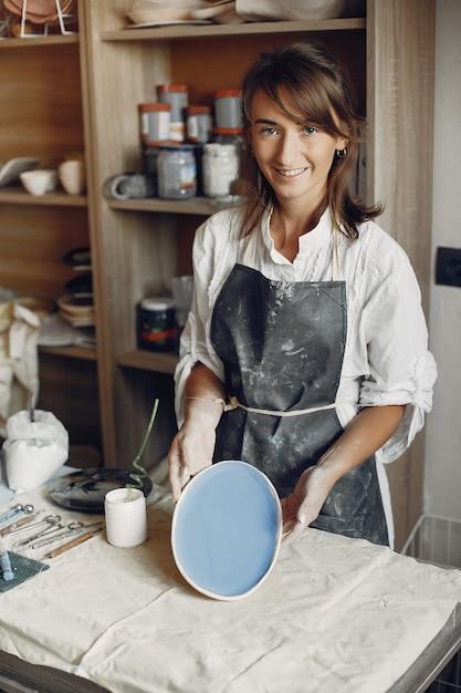 Jonge vrouw maakt aardewerk in werkplaats Gratis Foto