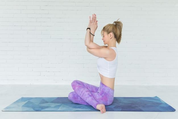 Jonge vrouw mediteert tijdens het beoefenen van yoga Premium Foto