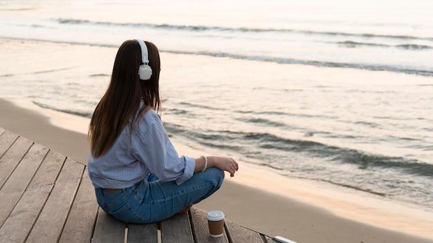 Jonge vrouw mediteren naast zee terwijl ze een koptelefoon draagt Gratis Foto