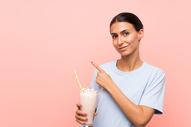 Jonge vrouw met aardbeimilkshake over geïsoleerde roze muur die aan de kant richt om een product te presenteren Premium Foto