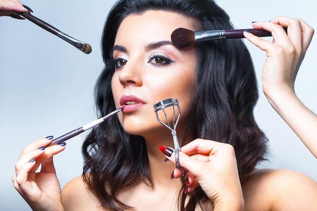 Jonge vrouw met allerlei make-up tools Premium Foto