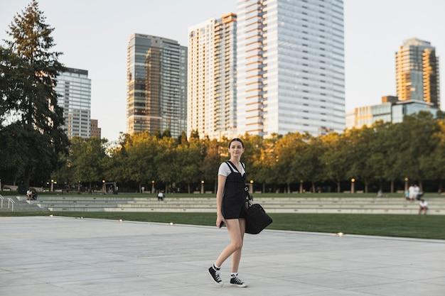 Jonge vrouw met bagage op stadspark Gratis Foto