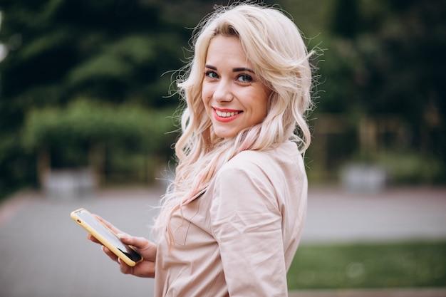Jonge vrouw met behulp van de telefoon buiten in het park Gratis Foto