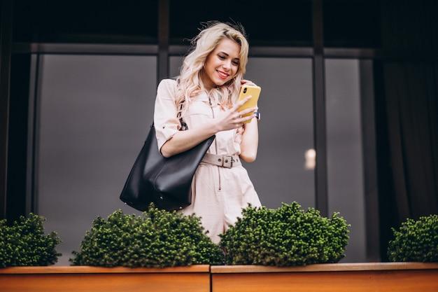 Jonge vrouw met behulp van de telefoon buiten Gratis Foto