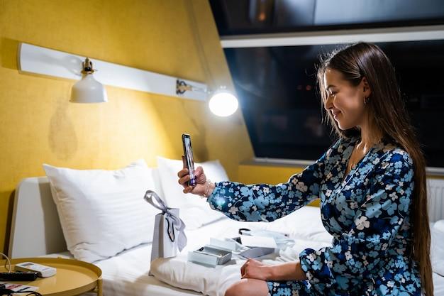 Jonge vrouw met behulp van mobiele smartphone. gelukkig lachend mooi meisje op bed in slaapkamer neemt selfie Gratis Foto