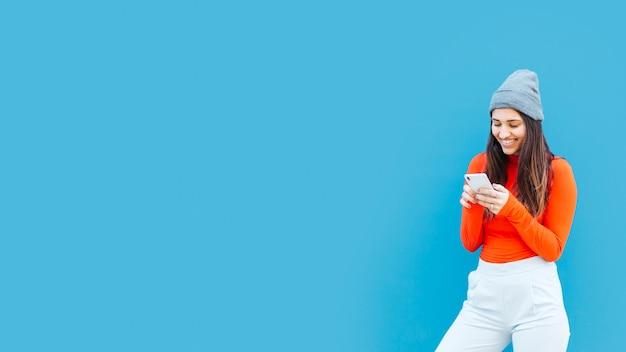 Jonge vrouw met behulp van mobiele telefoon op blauwe achtergrond met kopie ruimte Gratis Foto