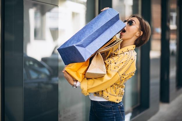 Jonge vrouw met boodschappentassen in de stad Gratis Foto