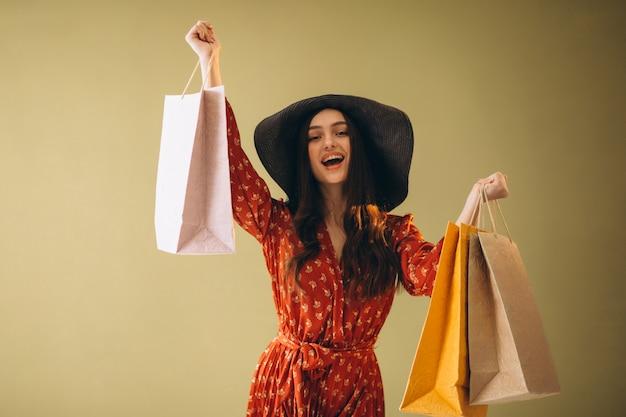 Jonge vrouw met boodschappentassen in een mooie jurk en hoed Gratis Foto