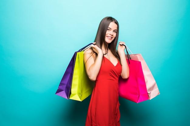 Jonge vrouw met boodschappentassen in rode jurk op blauwe muur Gratis Foto