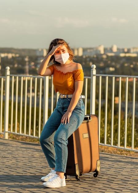 Jonge vrouw met bruin haar die een chirurgisch masker draagt dat op haar koffer in park zit terwijl zij weg kijkt. Premium Foto
