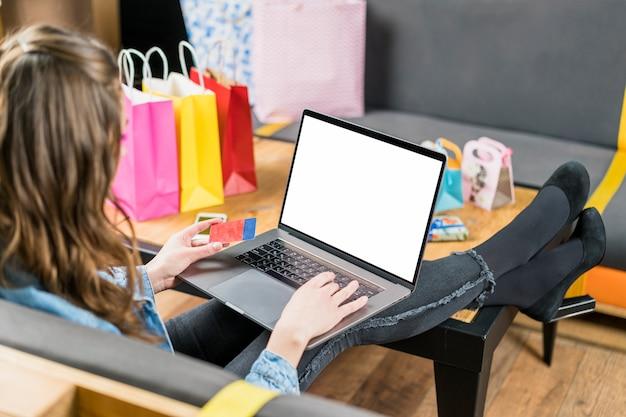Jonge vrouw met creditcard voor de betaling van online winkelen op laptop Gratis Foto