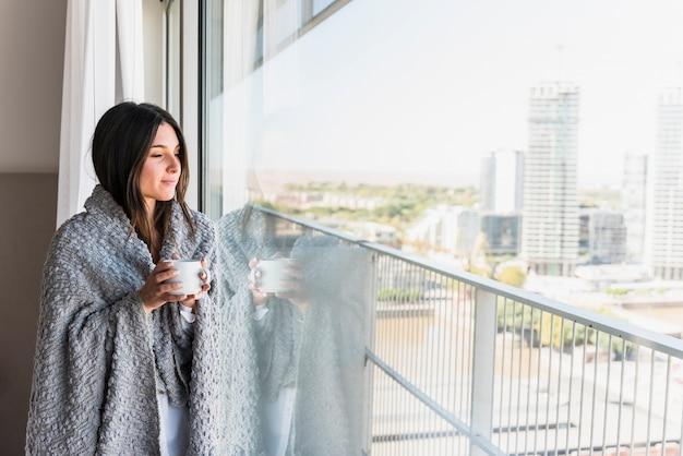 Jonge vrouw met deken over haar in hand de koffiekop die van de schouderholding weg kijken Gratis Foto