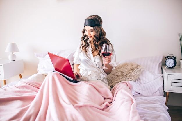 Jonge vrouw met donker haar zittend op bed in de slaapkamer en kijken naar film op laptop. alleen. rode wijn drinken. genieten van het leven. Premium Foto