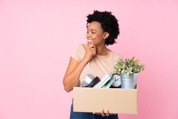 Jonge vrouw met dooshoogtepunt van dingen over geïsoleerde muur Premium Foto