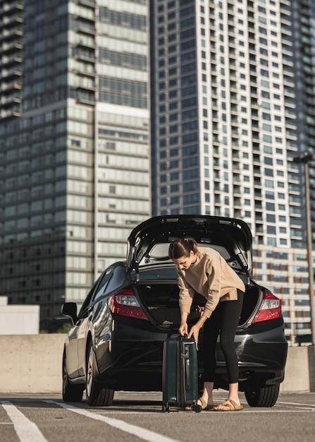 Jonge vrouw met een auto en een koffer Gratis Foto