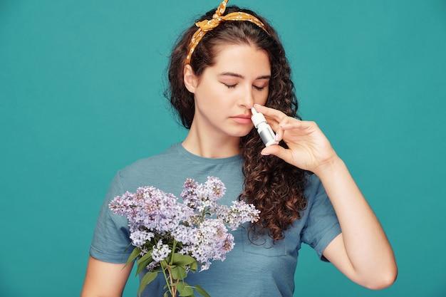 Jonge vrouw met een bos van lila die anti-allergische medicijnen in de neus spuiten terwijl ze voor de camera tegen een blauwe muur staat Premium Foto