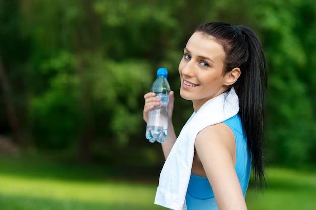Jonge vrouw met een fles water Gratis Foto