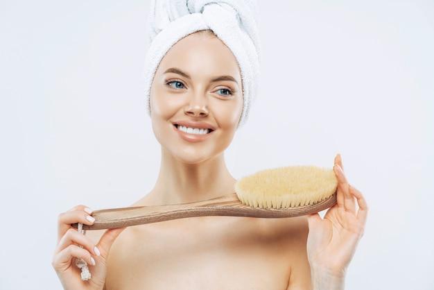 Jonge vrouw met een gezonde frisse huid, gebruikt lichaamsborstel, glimlacht zachtjes, draagt een badhanddoek op het hoofd, vormt topless, geïsoleerd op witte achtergrond. spa-accessoires. vrouwen, lichaamsverzorging, hygiëneconcept Premium Foto