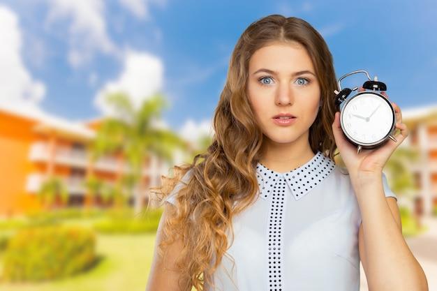 Jonge vrouw met een klok. tijd management concept Premium Foto