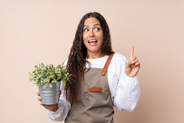 Jonge vrouw met een plant die de oplossing wil realiseren terwijl ze een vinger opheft Premium Foto