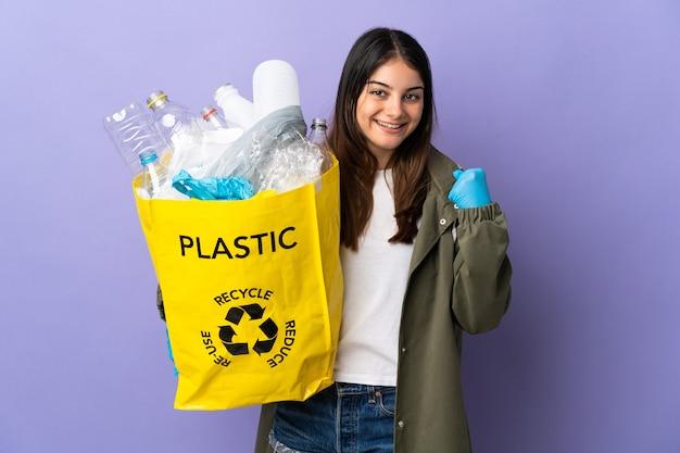 Jonge vrouw met een zak vol plastic flessen om te recyclen geïsoleerd op paars viert een overwinning in de winnaarspositie Premium Foto