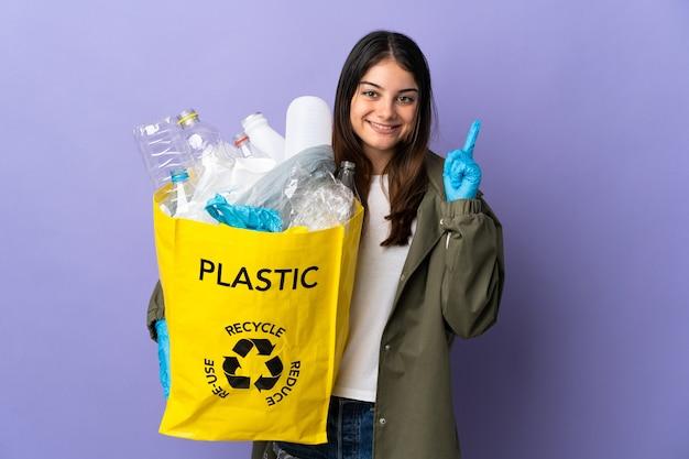 Jonge vrouw met een zak vol plastic flessen om te recyclen geïsoleerd op paars wijst op een geweldig idee Premium Foto