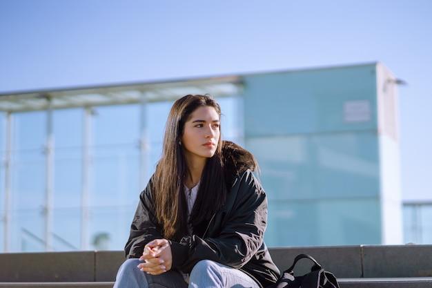 Jonge vrouw met een zwarte jas zittend op betonnen trappen met gebalde handen opzij op zoek Gratis Foto