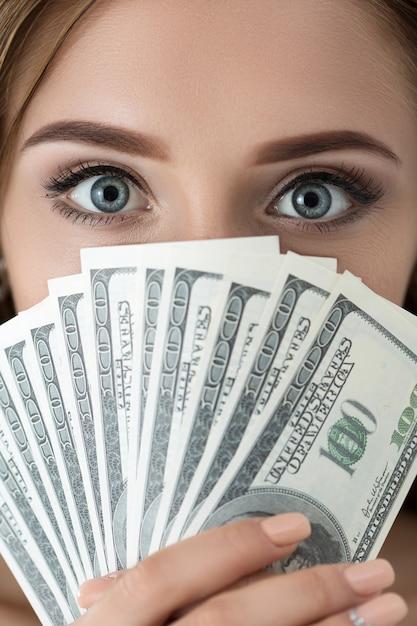 Jonge vrouw met fan van honderd dollarbiljetten portret. close-up shot van ogen Premium Foto