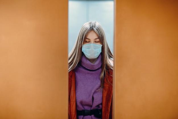 Jonge vrouw met gesloten ogen die zich in lift in medisch masker bevinden. deuren gaan dicht. coronavirus covid-19 pandemisch concept. Premium Foto