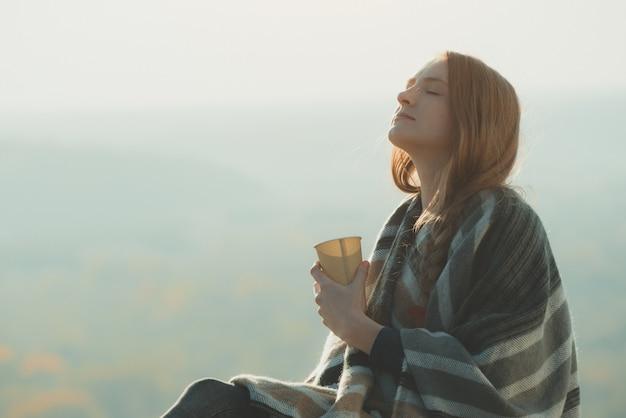 Jonge vrouw met gesloten ogen geniet van de lucht. papieren beker in handen, zonnige dag Premium Foto