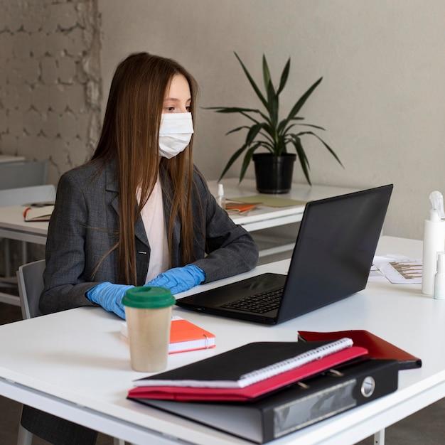 Jonge vrouw met gezichtsmasker op kantoor werken Gratis Foto