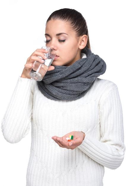 Jonge vrouw met glas water dat pillen neemt. Premium Foto