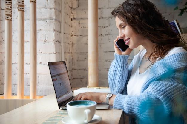 Jonge vrouw met golvend haar in warme blauwe gebreide trui praat aan de telefoon en het schrijven van notities tijdens het drinken van gezonde hete blauwe koffie latte gemaakt van natuurlijke vlindererwtthee. schoonheid en welzijn Premium Foto
