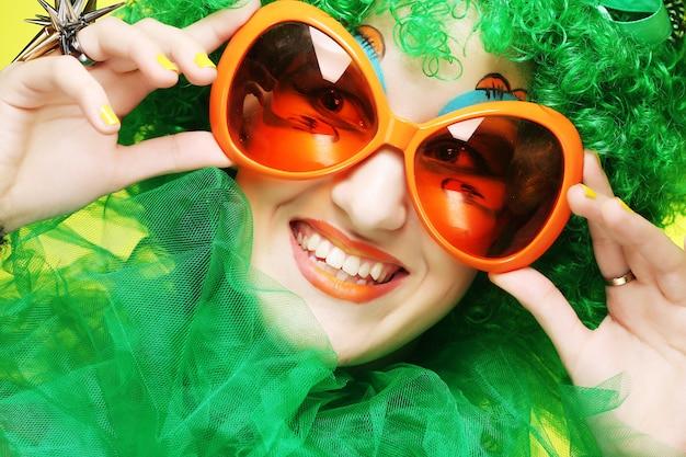 Jonge vrouw met groen haar en carnavalglazen Premium Foto