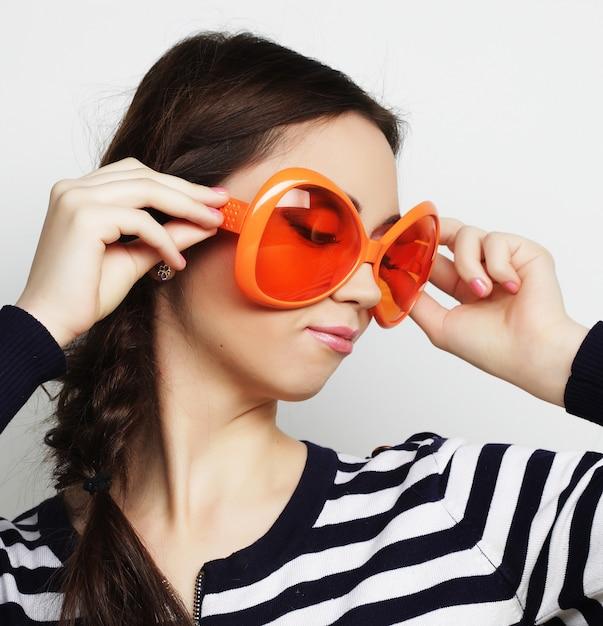 Jonge vrouw met grote oranje zonnebril Premium Foto