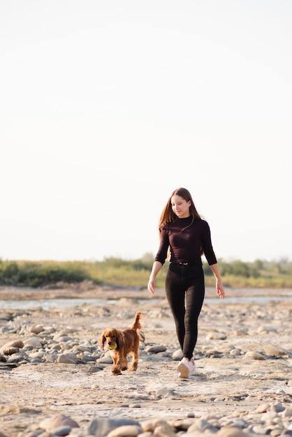 Jonge vrouw met haar hond wandelen Gratis Foto