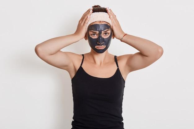 Jonge vrouw met haarband schoonheid gezichtsmasker dragen en poseren geïsoleerd over witte muur die lijden aan hoofdpijn of migraine, handen op het hoofd houden. Gratis Foto