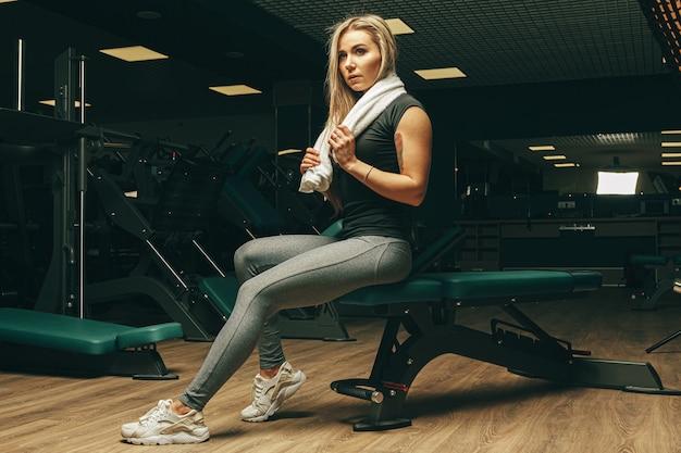 Jonge vrouw met handdoekzitting en het rusten in een gymnastiek Premium Foto
