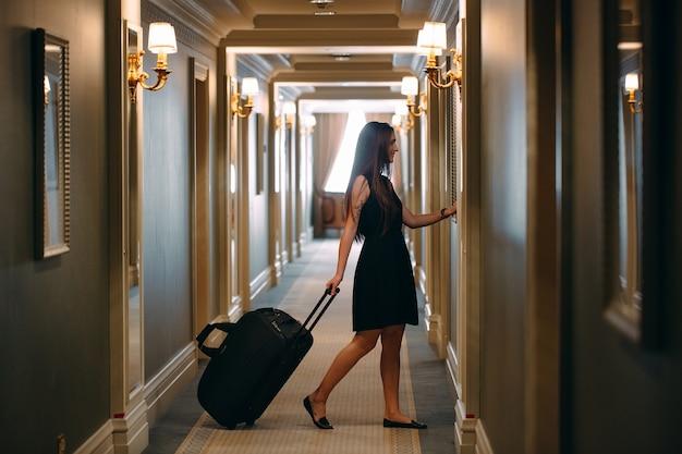 Jonge vrouw met handtas en koffer in een elegant pak loopt de hotelgang naar haar kamer. Premium Foto