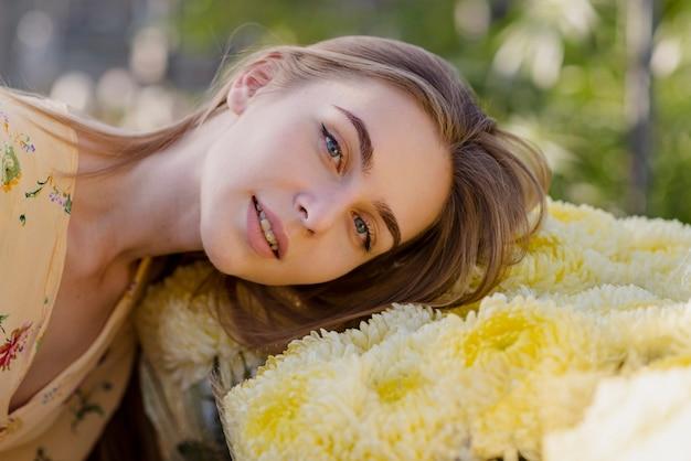 Jonge vrouw met hoofd op bloemen Gratis Foto