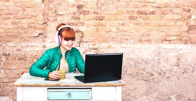 Jonge vrouw met hoofdtelefoons die laptop met behulp van op huiskantoor Premium Foto