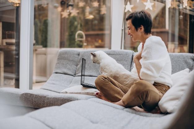 Jonge vrouw met kat die op laptop van huis werkt Gratis Foto